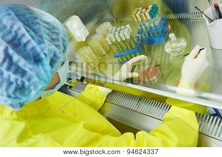 female science researcher in protective uniform and equipment works with dangerous hazard virus material at microbilogy laboratory