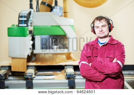 Portrait of industrial carpenter worker operating wood cutting machine during wooden door furniture manufacturing