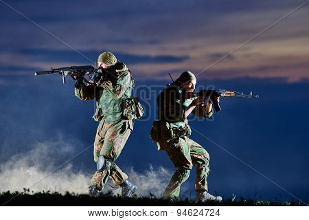 military. two soldiers in uniform running with assault rifle weapon on sunset during attack outdoors. Authentic shooting in challenging conditions. Maybe little blurred.