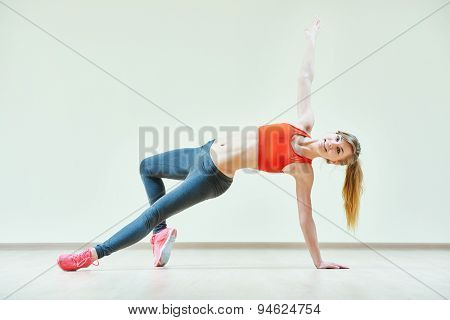 fitness instructor doing pilates or dancing exercises in sport club