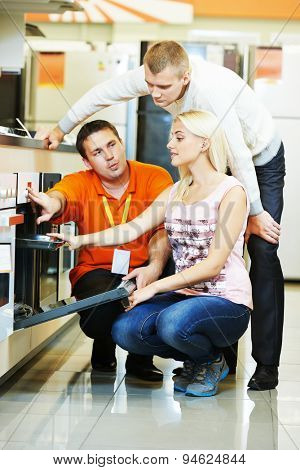 Seller assistant demonstrating cooker stove to young family in home appliance shopping mall supermarket