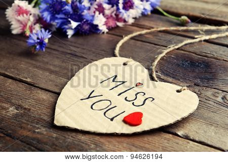 Written message with dry flowers on wooden table close up