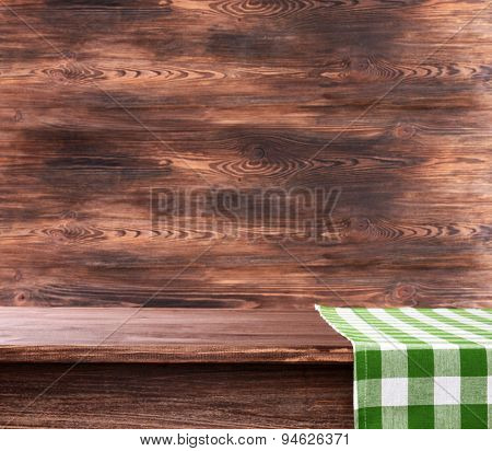 Empty wooden table with napkin on brown background