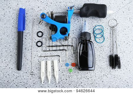 Tattoo machine and tattoo Supplies, on grey background