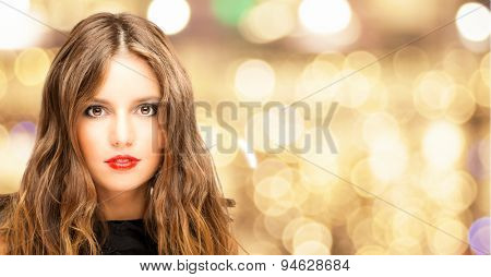 Fashion portrait of a young woman against a gold bokeh background