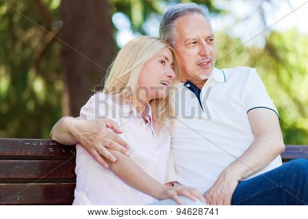 Mature couple hugging on a bench