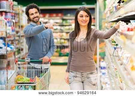 Man asking his girlfriend to buy a product in a supermarket
