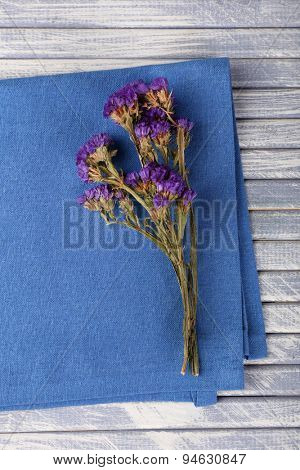 Beautiful dry flowers on napkin on wooden table close up