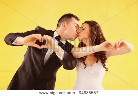 Bride And Groom Making Heart Shape With Their Hands