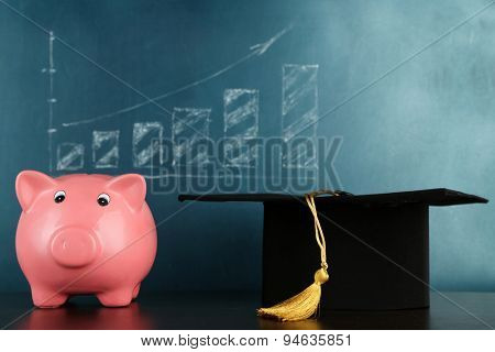 Piggy bank with grad hat on blackboard background