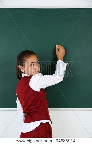 Beautiful little girl writes on blackboard in classroom