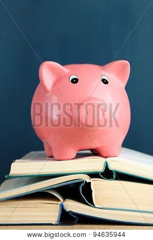 Piggy bank with books on blackboard background