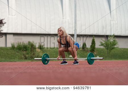 Healthy Young Woman Doing Exercise For Back Outdoor