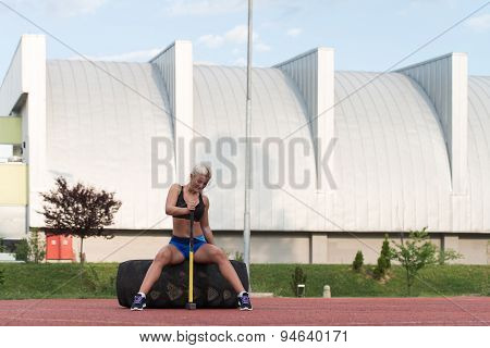 Young Woman With Hammer And Tire Resting