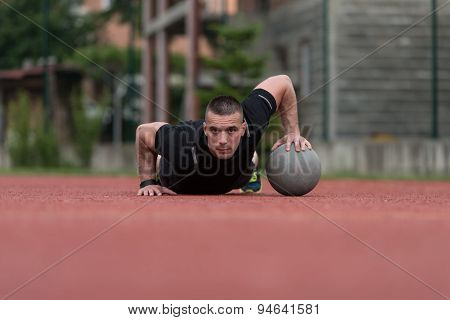 Young Man Exercising Push-ups On Medicine Ball Outdoor
