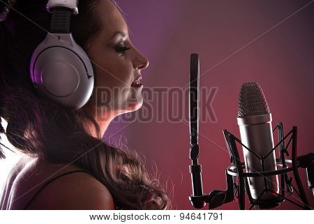 Young singer screaming on the studio microphone
