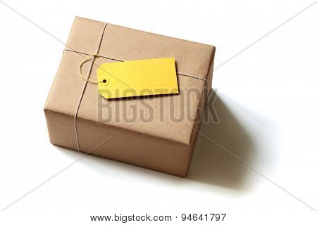 Gift package wrapped in brown recycled paper with blank yellow label isolated on white