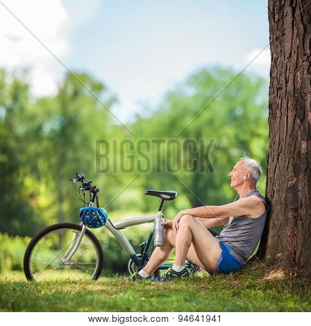 Senior cyclist sitting by a tree in a park with a water bottle in his hand and listening to music on headphones shot with tilt and shift lens
