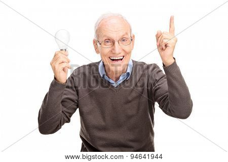 Joyful senior holding a light bulb and gesturing with his hand as if he is having an idea isolated on white background