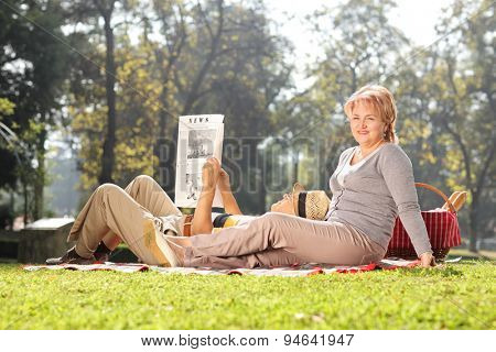 Mature woman posing in a park with her husband lying on her lap and reading a newspaper on a beautiful sunny day