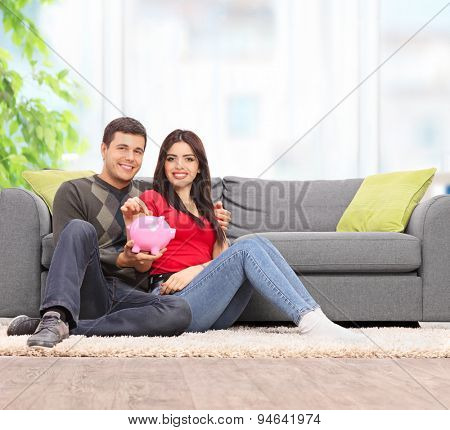 Young couple posing with a piggybank seated on the floor by a gray sofa at home shot with tilt and shift lens