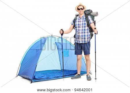 Young cheerful hiker carrying a backpack and posing in front of a blue tent isolated on white background