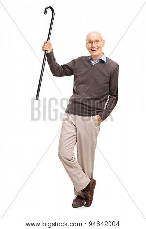 Full length portrait of a senior gentleman showing his cane and leaning against a wall isolated on white background