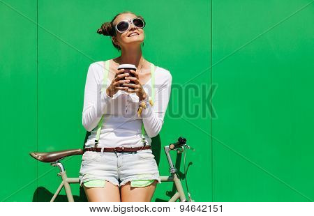 Fashionable beautiful young Pretty girl in shorts and t-shirt and cool sunglasses stands with  bicyc