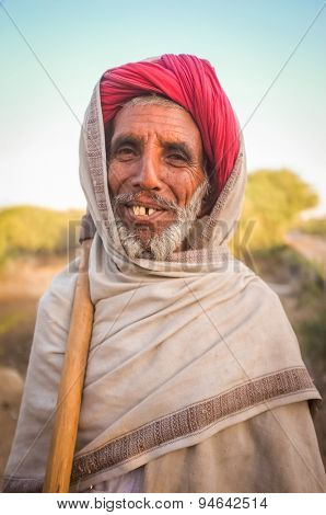 GODWAR REGION, INDIA - 14 FEBRUARY 2015: Elderly Rabari tribesman stands with axe on sholder. Rabari or Rewari are an Indian community in the state of Gujarat.
