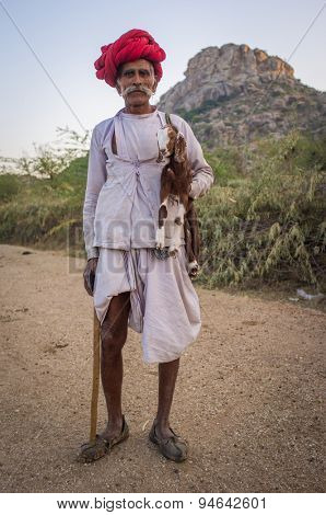 GODWAR REGION, INDIA - 13 FEBRUARY 2015: Elderly Rabari tribesman stands and holds goatling and traditional axe. Rabari or Rewari are an Indian community in the state of Gujarat.