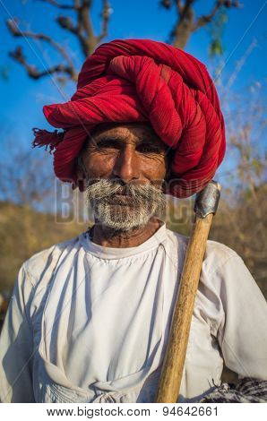 GODWAR REGION, INDIA - 13 FEBRUARY 2015: Rabari tribesman holds traditional axe and stands on field. Rabari or Rewari are an Indian community in the state of Gujarat.