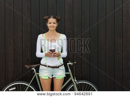 Pretty girl in shorts and t-shirt stands with her bicycle fix gear near the wall of wooden planks br
