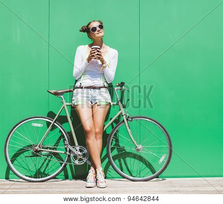 Fashionable beautiful young Pretty girl in shorts and t-shirt and sunglasses stands with  bicycle fi