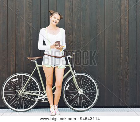 Pretty girl in shorts and t-shirt stands with bicycle fix gear near the wall of wooden planks bright