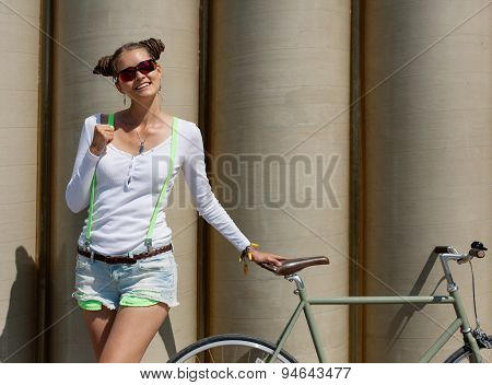 Pretty girl in shorts and t-shirt, in sunglasses stands with bicycle fix gear the posing against a b