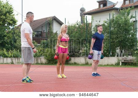 Two People Doing Kettlebell Exercise Outdoor With Instructor