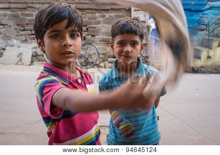 JODHPUR, INDIA - 17 FEBRUARY 2015: Two boys on street fool around with mop.