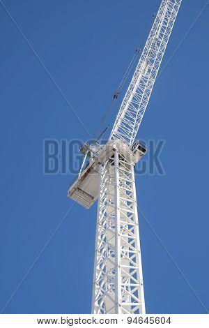 white tower crane against blue sky