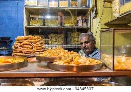 JODHPUR, INDIA - 16 FEBRUARY 2015: Vendor sits in store with various food on metal plates and noodles on shelves.