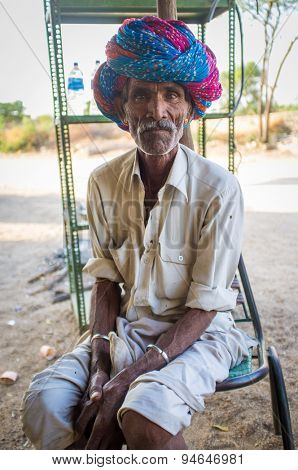 GODWAR REGION, INDIA - 13 FEBRUARY 2015: Indian tribesman sits on chair in chai shop with colorful turban on head.