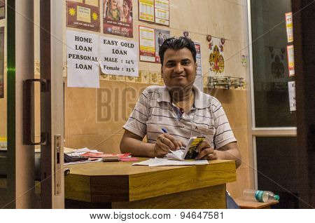 JODHPUR, INDIA - 16 FEBRUARY 2015: Indian man sits in Gold loan office and writes on notebpad.