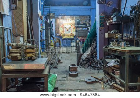 JODHPUR, INDIA - 17 FEBRUARY 2015: Empty mechanics shop with small shiva temple in background.