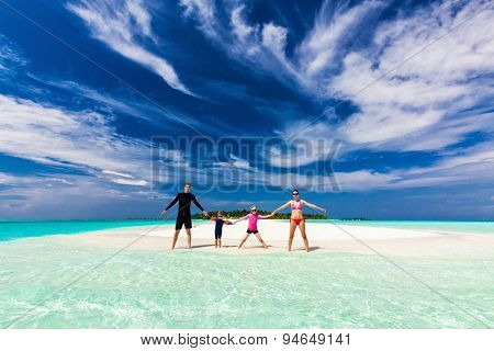Happy family standing on the tropical sandy beach holding hands