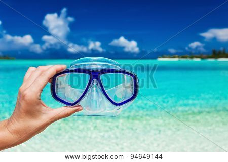 Hand holding snorkel googles against blurred beach and blue sky