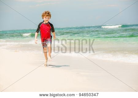 Cute 7 years old boy in red rushwest swimming suit enjoing summer time at tropical beach with white