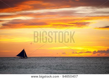 Sailing boat over beautiful orange sunset
