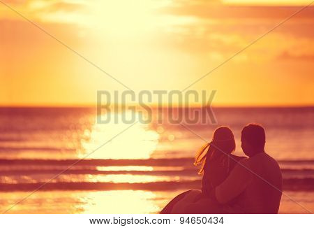 Romantic couple looking sunset over sea