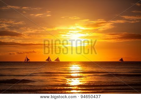 Nature background, beautiful sunset with reflection in sea with sailboat