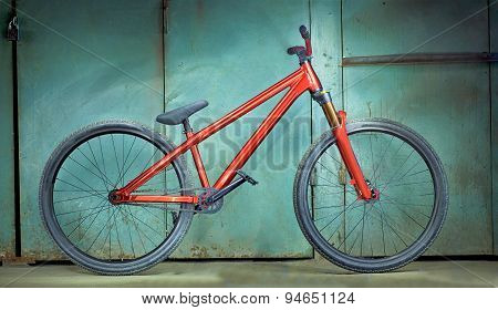 Red bicycle on a green garage background