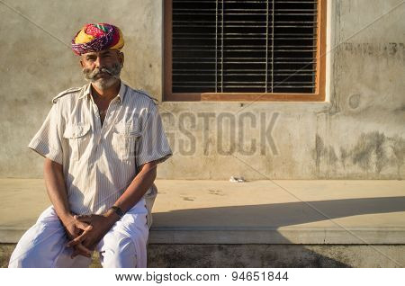 GODWAR REGION, INDIA - 14 FEBRUARY 2015: Adult Indian man with colorful turban and curled mustache sits in street.